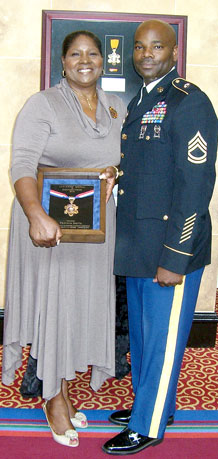 "Courtesy photo.   Sgt. 1st Class Travion Smith and his mother, Sharon Caleb, show the ""Citizen's Medal of Distinction"" Smith earned from the Colorado Springs Police Department, recognizing his heroism and selfless service in saving the life of a young accident victim."