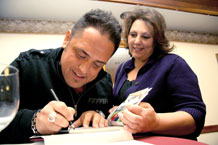 Biggest Loser season nine-winner Michael Ventrella signs a Biggest Loser book for Malaine Heale, Fort Carson Family member and Evans Army Community Hospital employee, following his health and lifestyle change presentation Jan. 21 at the Elkhorn Conference Center.