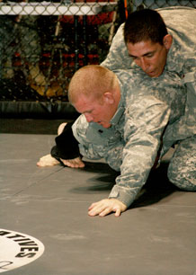 Photo by Kerstin Lopez.  Sgt. 1st Class Keith Sieraki, 759th Military Police Battalion, top, goes head-to-head with 1st Lt. Tim Palmer, 4th Brigade Combat Team, 4th Infantry Division, bottom, for the title of cruiserweight division champion.
