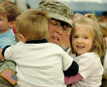 Photo by Sgt. Craig Cantrell.  Staff Sgt. David Evans, 3rd Special Troops Battalion, 3rd Brigade Combat Team, 4th Infantry Division, hugs his son and daughter during the welcome home ceremony Feb. 1 at the Special Events Center.