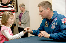 Megan Coleman, 4, receives a sticker from NASA astronaut Col. Douglas H. Wheelock during his visit to Fort Carson March 10 at the USO. The sticker is a copy of the space shuttle Discovery mission insignia, which Wheelock wears on his uniform.