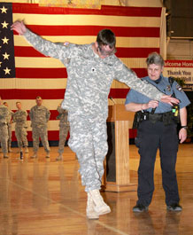 "Spc. Jaycee Seaman, 1st Battalion, 8th Infantry Regiment, 3rd Brigade Combat Team, 4th Infantry Division, tries to walk a straight line wearing ""drunk"" goggles while Colorado Springs police officer Pat Turechek administers a sobriety test at a safety briefing April 1 in the Special Events Center."