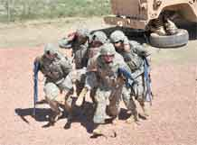 "Soldiers from the 544th Engineer Company, 52nd Engineer Battalion, four-man carry an ""injured"" troop to a covered, secure position during a Mountain Post Medical Simulation Training Center Tactical Combat Casualty Care training lane demonstration following the facility's ribbon-cutting ceremony Sept. 2."