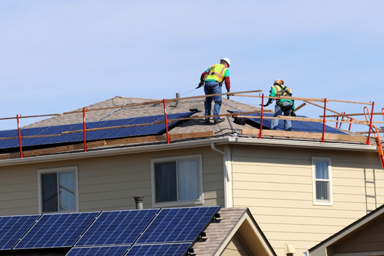 (U.S. Air Force photo/Staff Sgt. Aaron Breeden) PETERSON AIR FORCE BASE, Colo. – Contractors at Tierra Vista Communities scale the rooftop of a residence in base housing to test solar panels that were installed over the summer. The panels were installed as part of a 20-year lease that is expected to save more than $1.1 million in energy costs. These savings will provide additional funds for neighborhood improvements.