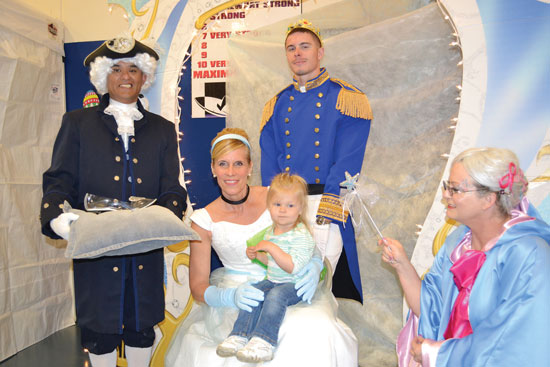 U.S. Air Force photo/Brian Hagberg Characters from Cinderella pose for a photo with a Team Schriever member during the 14th annual Spring Fling Saturday in the fitness center gym at Schriever Air Force Base, Colo. The 50th Force Support Squadron hosted the event, which drew a record 1,750 people, for children and family members of Schriever personnel.