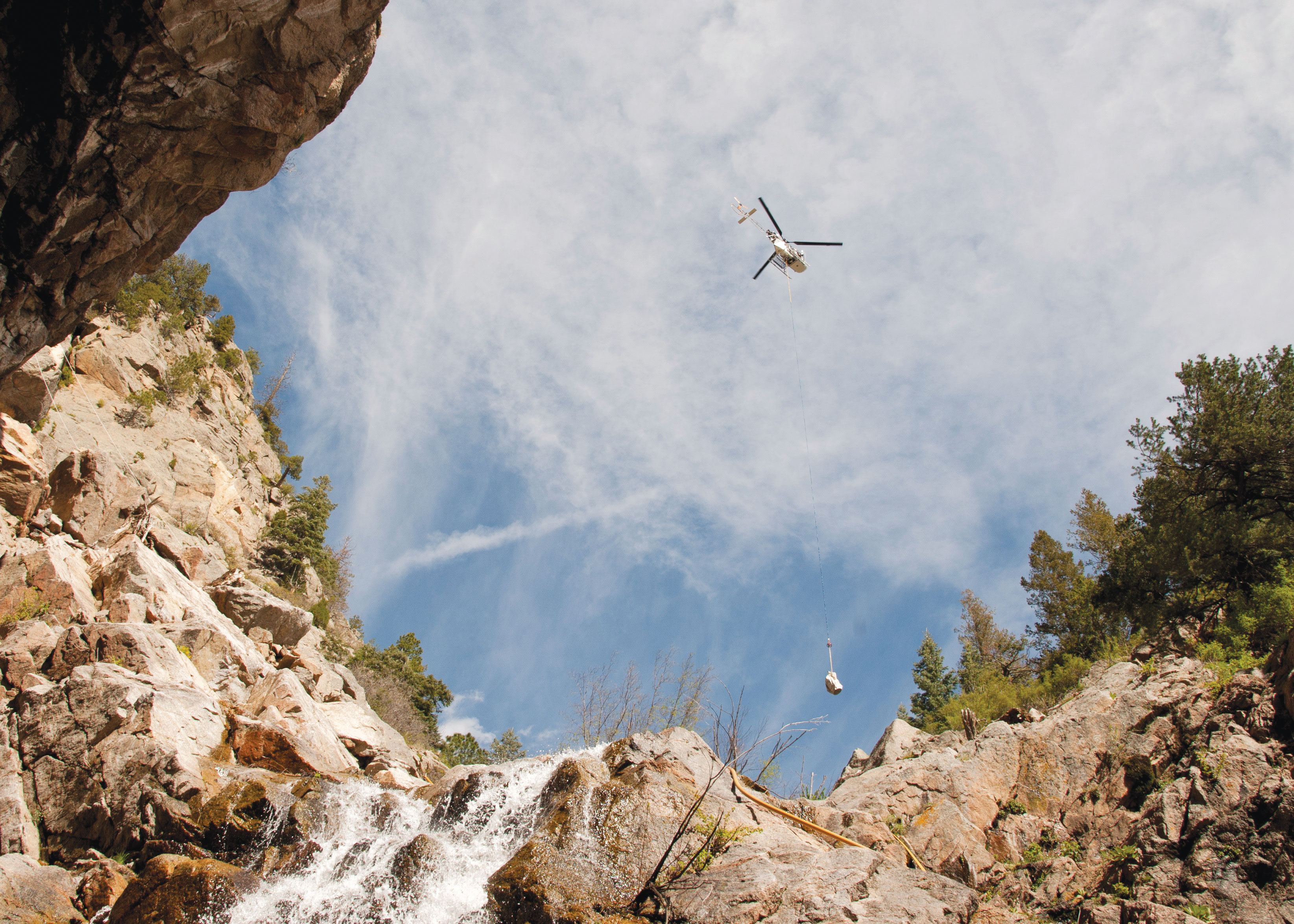 "(U.S. Air Force photo by Senior Airman Tiffany DeNault) CHEYENNE MOUNTAIN AIR FORCE STATION, Colorado – A ""Lama"" helicopter designed for high elevation, lifts equipment in and out of the canyons where ring nets are to be installed, May, 28, 2015. The five ring nets are one of four steps in the mitigation process to reduce the damage of future landslides. The ring nets, 15-foot deep main catchment basin, a culvert down the mountain into the storm water system and infrastructure protection are being built as a result of landslides that struck the mountain Sept. 12, 2013, following torrential rain."