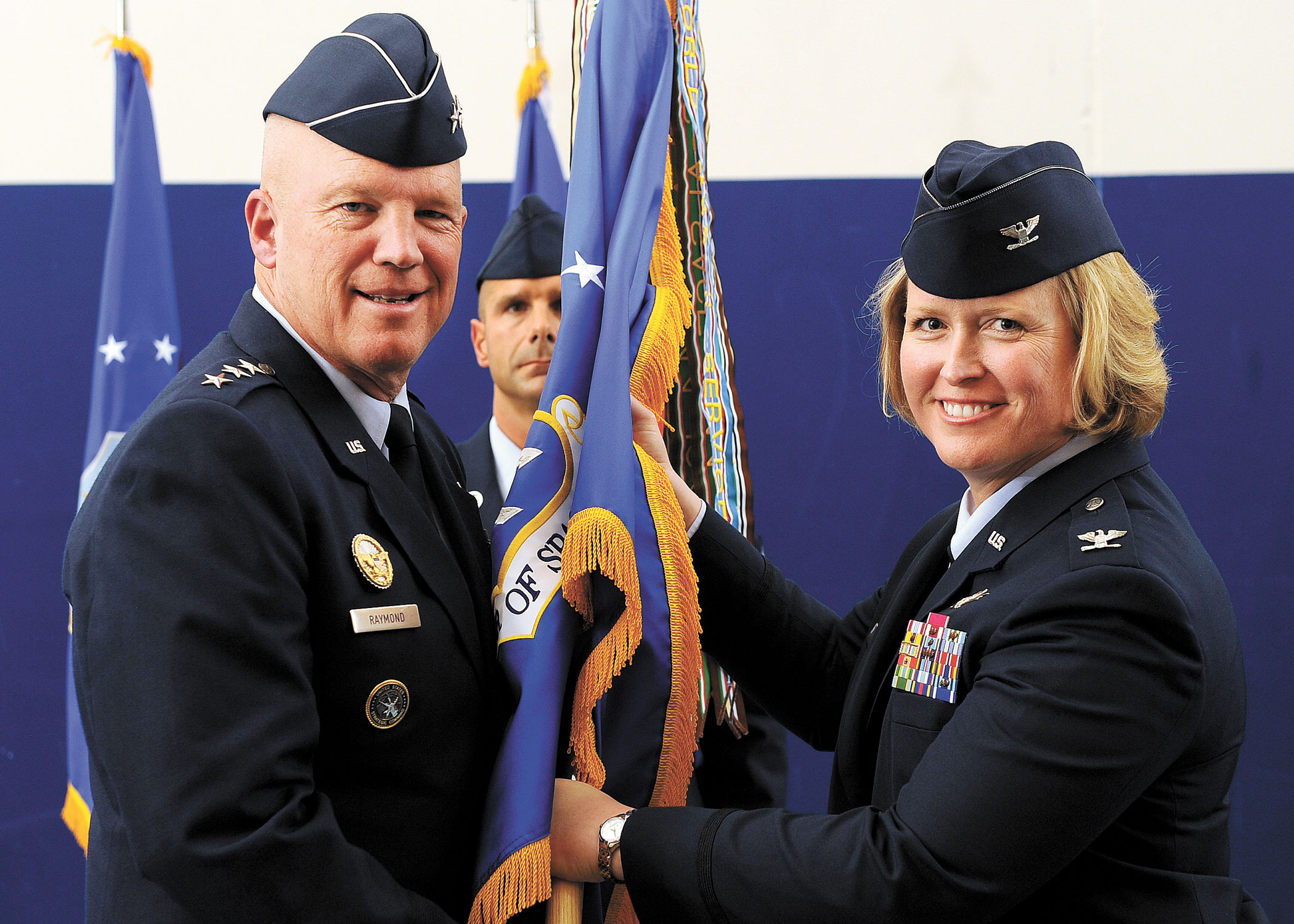 "U.S. Air Force photo/Dennis Rogers U.S. Air Force Lt. Gen. John W. ""Jay"" Raymond, commander, 14th Air Force (Air Forces Strategic) and Joint Functional Component Command for Space, passes the guidon to Col. DeAnna M. Burt, as she assumes command of the 50th Space Wing, during the change-of-command ceremony Friday at Schriever Air Force Base, Colo. As wing commander, Burt will be responsible for more than 4,200 military, Department of Defense civilians and contractor personnel serving at 14 operating locations worldwide and operating 69 surveillance, navigation and timing, space situational awareness and satellites valued at more than $66 billion."
