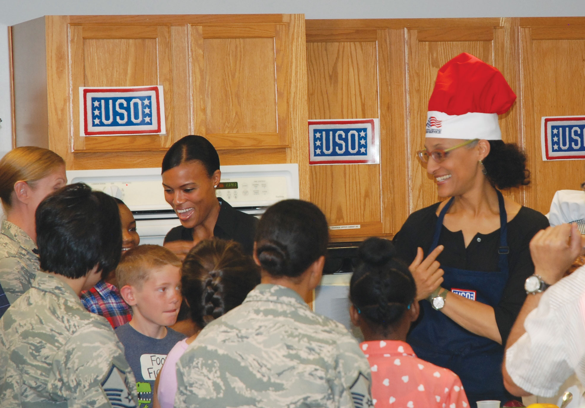 "(U.S. Air Force photo by Dave Smith) TV chef Carla Hall, co-host of ABCs ""The Chew,"" is pleased with the answer given by one of the youngsters participating in her cooking class held at the Health and Wellness Center at Peterson Air Force Base on June 22. Hall was on a USO tour of Colorado, also holding similar sessions at Fort Carson and the U.S. Air Force Academy."