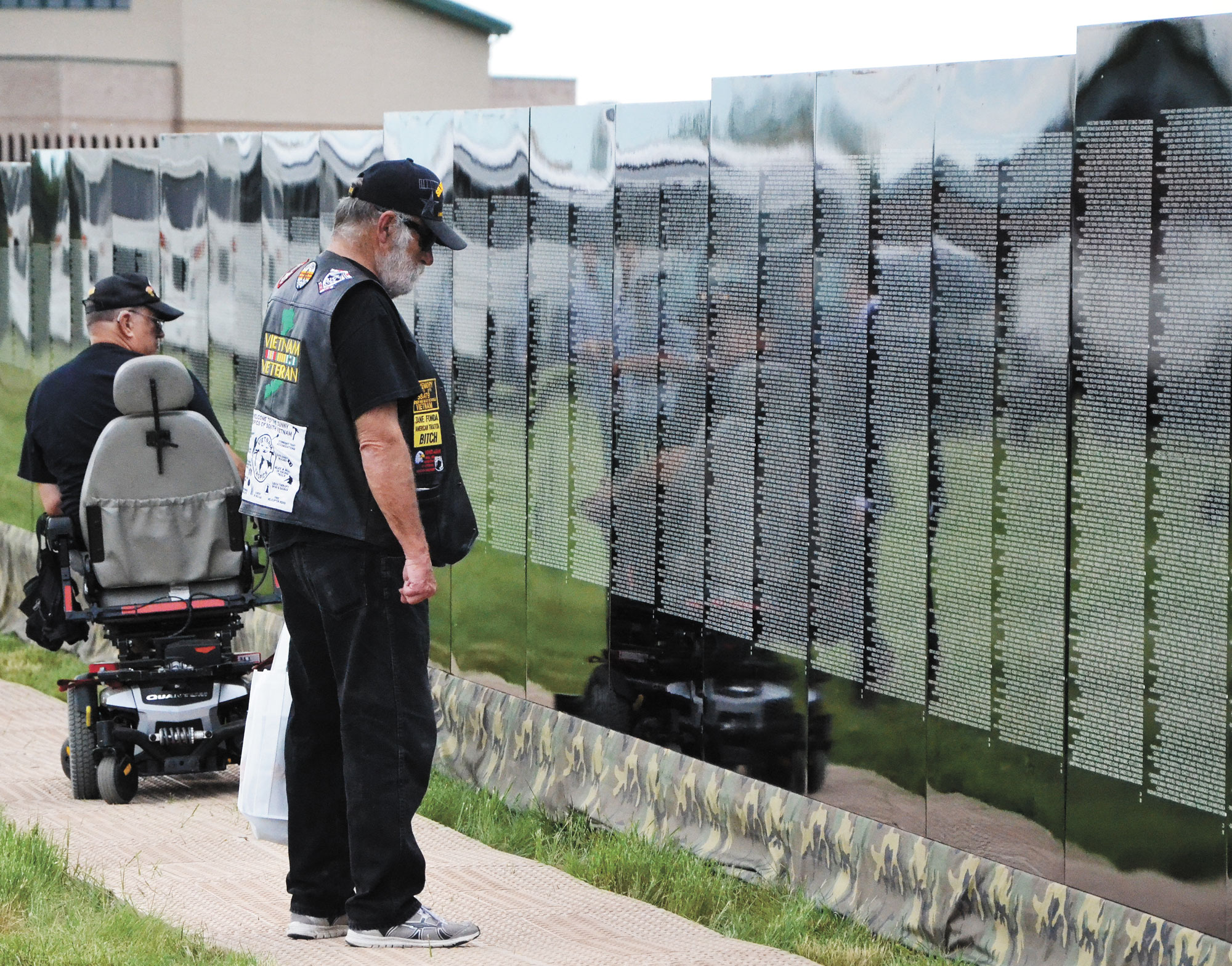 "U.S. Air Force photo/Brian Hagberg Vietnam veterans pause to reflect in front of the names of fallen comrades at ""The Moving Wall"" Thursday, June 11, 2015 at Kit Carson Memorial Park, Colo. ""The Moving Wall"" is a half-size replica of the Vietnam Veterans Memorial in Washington, D.C. that travels the country in order to give people who can't make it to Washington an opportunity to experience the Memorial."