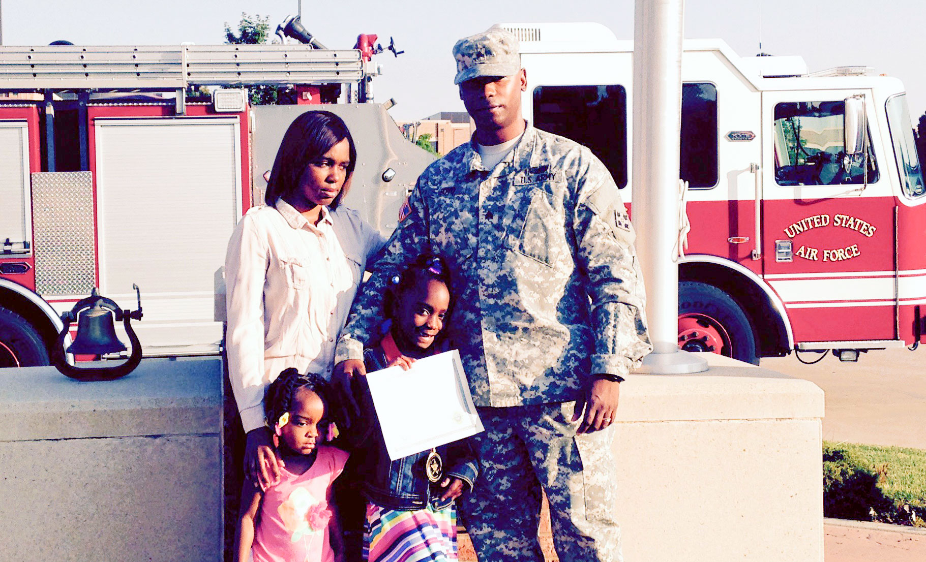 In a moment away from the spot light Sanyla Boyd is surrounded by sister Shaian, 3, mother Tranise and father, U.S. Army Sgt. Michael Boyd after receiving the inaugural 911 Award for Heroism by Peterson Air Force Base Fire Emergency Services on June 26, 2015. The award recognized her calm in the face of an emergency when her mother collapsed with chest pain May 14, 2015. Her quick action probably saved her mother's life. (U.S. Air Force photo by Dave Smith)