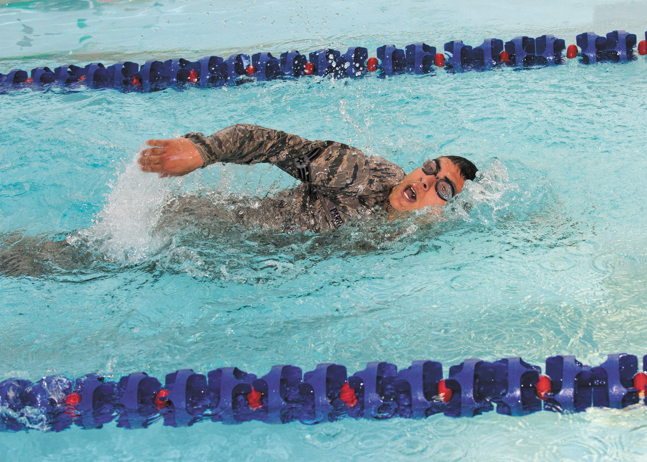 U.S. Air Force photo/Airman 1st Class Rose Gudex Senior Airman Brian Parra, 2nd Space Operations Squadron satellite systems operator, swims the 100 meter swim to see if he qualifies for the German Armed Forces Proficiency Badge at the Iron Horse Sports and Field Center at Fort Carson, Tuesday, June 30, 2015. The event required participants to complete the swim in less than four minutes while wearing their military uniform and a physical training uniform underneath. After the swim was completed, they had to successfully remove their outer uniform without touching the sides of the pool to pass the event.