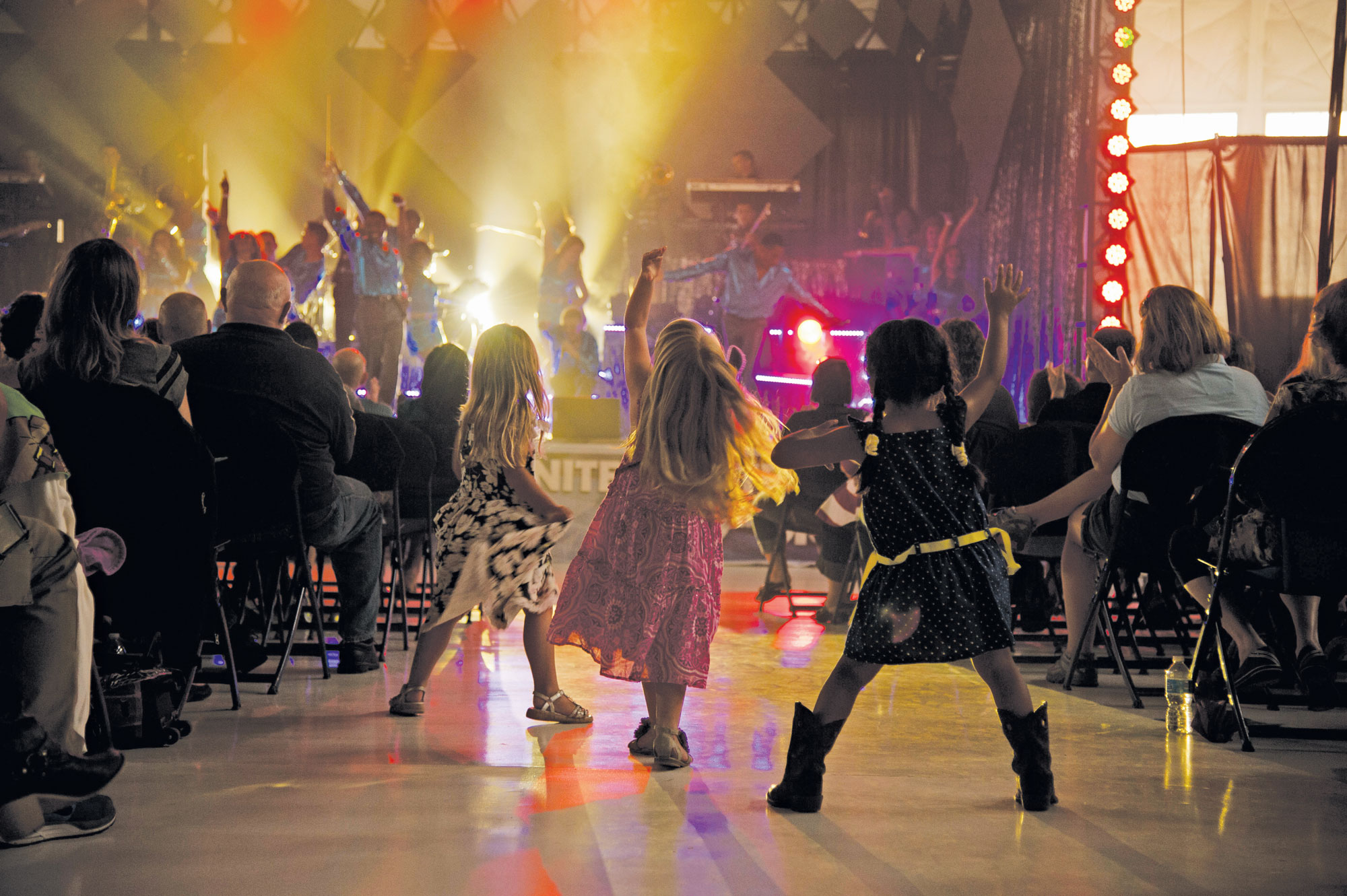 (U.S. Air Force Senior Airman Tiffany DeNault) PETERSON AIR FORCE BASE, Colo. – Children dance in the aisle during the Tops in Blue performance at Hangar 140, July 1, 2015. The Tops in Blue performers travel to 20 countries putting on 75 shows in seven months, promoting community relations, recruiting efforts and serving as ambassadors for the United States and the U.S. Air Force.