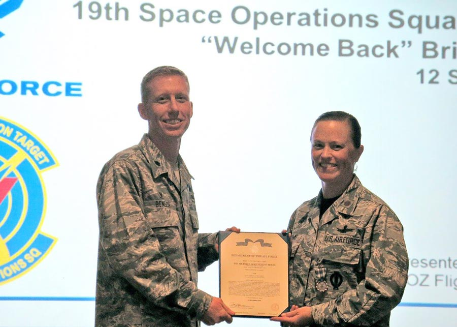 (Courtesy photo) Lt. Col. Todd Benson, 2nd Space Operations Squadron commander, presents the Air Force Achievement Medal and citation to Maj. Kimberly Adams, 19th Space Operations Squadron Operations Flight commander, during a Reserve Unit Training Assembly weekend Sept. 12, 2015, in the Building 300 auditorium at Schriever Air Force Base, Colorado. The medal was a complete surprise and was presented in front of the entire squadron and 310th Space Wing leadership, including the wing and group commanders.