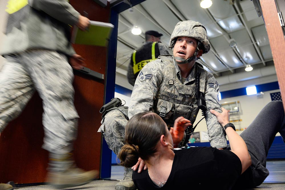 U.S. Air Force photo/Christopher DeWitt Senior Airman Anthony Tasker, 50th Security Forces Squadron, provides first aid to simulated shooting victim, Senior Airman Oceana Goodsell, 50 SFS, during an active shooter exercise Wednesday, Nov. 18, 2015, in the fitness center at Schriever Air Force Base, Colorado. The base engaged in a week-long exercise that tested and assessed emergency response forces' procedures while accomplishing the mission.