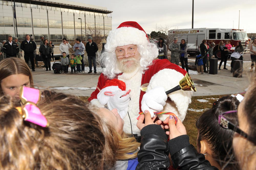 "U.S. Air Force photo/Dennis Rogers Santa Claus rings his bell and passes out candy canes to Ellicott Elementary School choir students during the tree lighting ceremony at Schriever Air Force Base, Colorado, Tuesday, Dec. 1, 2015. Santa journeyed down from the North Pole to help Team 5-0 ring in the holiday spirit and listen to the children sing some of his favorite Christmas Carols: ""Jingle Bells,"" ""Feliz Navidad,"" ""Jingle Bell Rock,"" ""Winter Wonderland"" and ""Santa Claus is Coming to Town."""