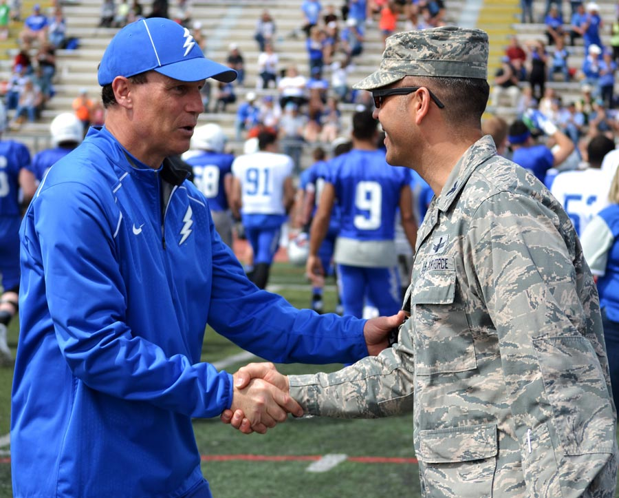 U.S. Air Force photo/Brian Hagberg Col. Anthony Mastalir (right), 50th Space Wing vice commander, shakes hands with U.S. Air Force Academy coach Troy Calhoun following the annual Blue-Silver game at Fountain-Fort Carson High School, Saturday, April 9, 2016. Mastalir was one of several installation commanders who served as an honorary coach for the game.