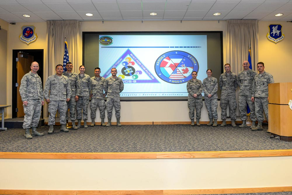 U.S. Air Force photo/Christopher DeWitt Col. Dennis Bythewood (left), 50th Operations Group commander, and Lt. Col. Chris Todd (second from left), 3rd Space Operations Squadron commander, present the eight Airmen selected to be part of the Launch and Early Orbit Teams for Wideband Global SATCOM-8 and 9 during a ceremony at Schriever Air Force Base, Colorado, Thursday, April 21, 2016. The Airmen endured a competitive selection process, which included knowledge-based tests, problem solving scenarios and interviews.