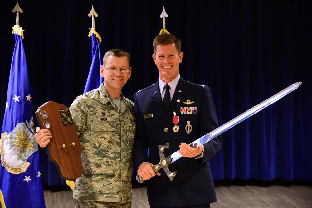 (U.S. Air Force photo by Staff Sgt. Amber Grimm) PETERSON AIR FORCE BASE, Colo. — Col. Reginald Ash, 21st Mission Support Group commander, presents a sword to Col. Richard Burchfield, 21st Space Wing Senior Individual Mobilization Augmentee, during his retirement ceremony at Peterson Air Force Base, Colo., June 10, 2016. Burchfield received several gifts and plaques recognizing his nearly 30 years of dedicated service to the U.S. Air Force.