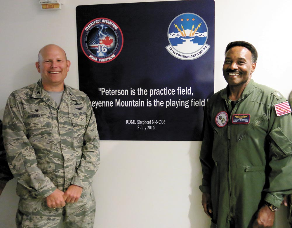 (Courtesy photo) CHEYENNE MOUNTAIN AIR FORCE STATION, Colo. – Rear Adm. Dwight Shepherd, North American Aerospace Defense and United States Northern Command cybersystems director, right, and Col. Gary Cornn, Cheyenne Mountain Air Force Station commander, present the newly unveiled sign honoring Shepherd's work related to network and software upgrades to the installation July 8, 2016. The quote was used to keep Shepehrd's team on track as the project is underway.