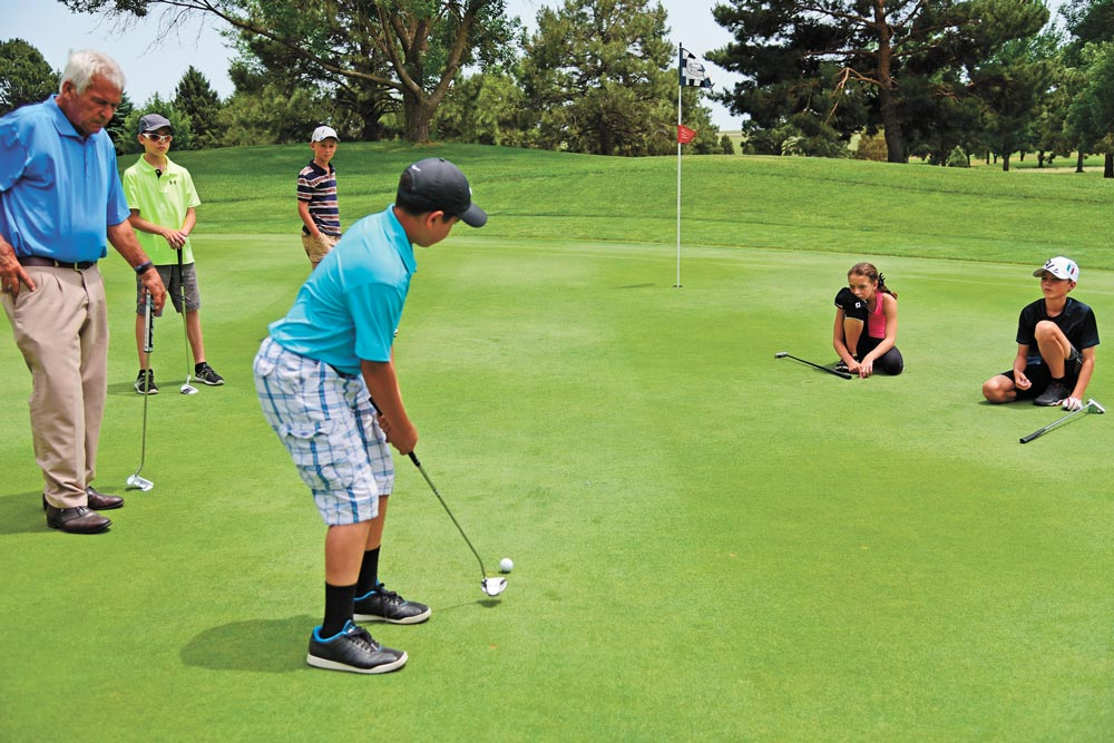 (U.S. Air Force photo by Staff Sgt. Amber Grimm) PETERSON AIR FORCE BASE, Colo. — Jack O'Brien, head golf professional at Silver Spruce Golf Course, helps Peterson youth work on their putting game June 22, 2016 at the base golf course. O'Brien went from a college football player to a business career before finding a passion for golf in his forties.