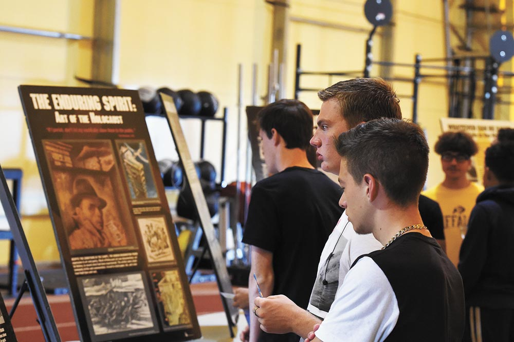 "U.S. Air Force photos/Airman William Tracy Ellicott High school students read informational poster boards in the ""Holocaust museum"" exhibit during Holocaust Remembrance Day at Schriever Air Force Base, Colorado, Tuesday, Aug. 23, 2016. The boards detailed important events during the Holocaust."