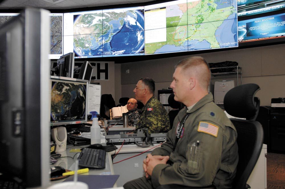 (Courtesy photo by Mike Kucharek) PETERSON AIR FORCE BASE, Colo. — Members of the North American Aerospace Defense Command and United States Northern Command monitor systems and networks in the NORAD and USNORTHCOM Command Center at Peterson Air Force Base. NORAD is the bi-national Canadian and American command that provides maritime warning, aerospace warning and aerospace control for Canada and the United States. USNORTHCOM is the joint combatant command formed in the wake of the 9/11 terrorist attacks, to provide homeland defense and defense support of civil authorities.