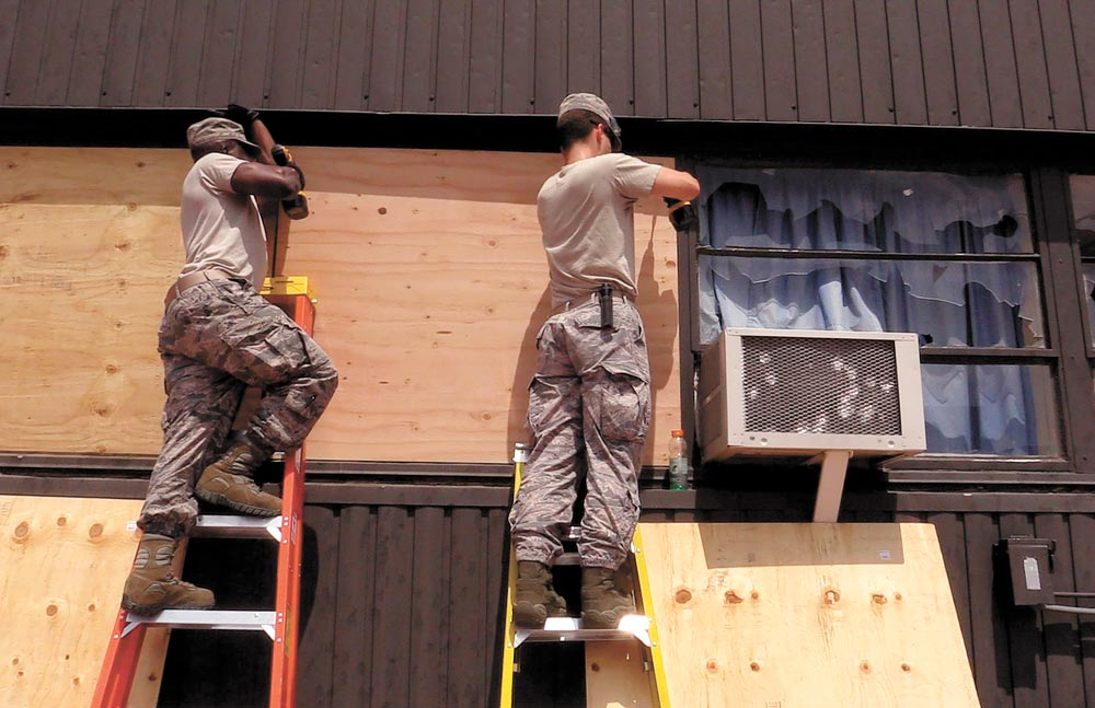 (Top) Airmen assigned to the 21st Civil Engineer Squadron board broken windows at Peterson Air Force Base, Colo., Aug. 1, 2016. Peterson AFB was hit by a storm carrying hail the size of baseballs.