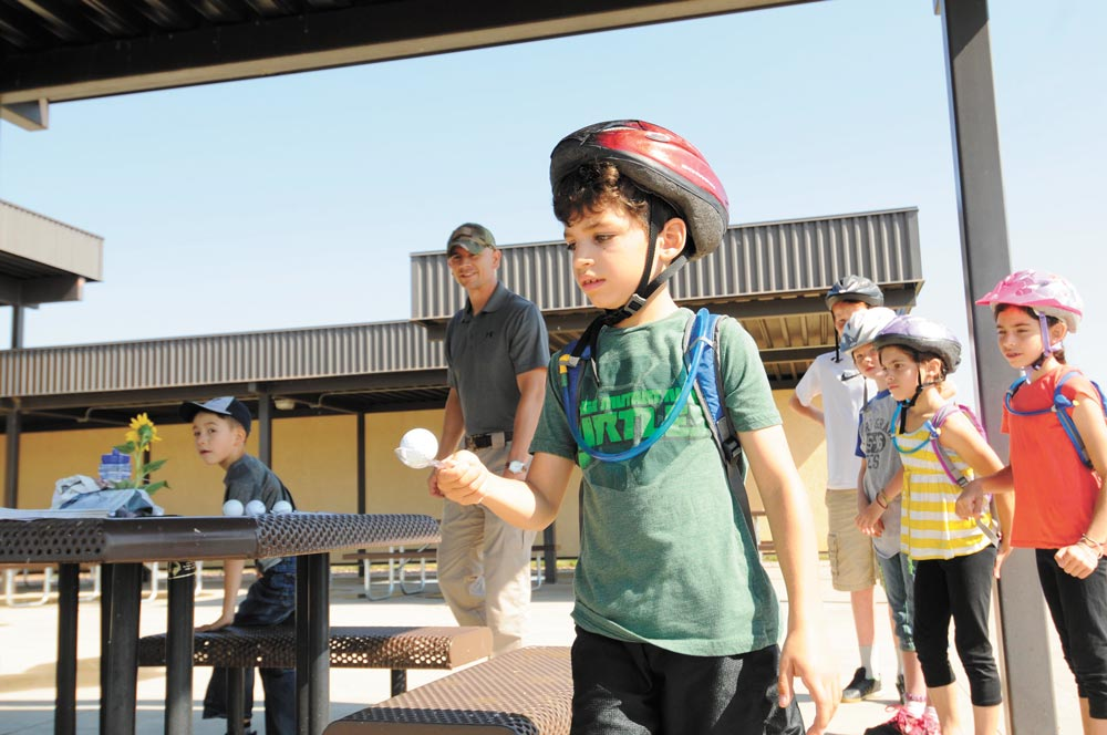 U.S. Air Force photo/2nd Lt. Darren Domingo Toby Janaros navigates obstacles while carrying an egg on a spoon during the Amazing gRace: Kids Edition at Schriever Air Force Base, Colorado, Saturday, July 30, 2016. The egg relay was one of eight stations teams had to successfully complete before finishing the scavenger hunt.
