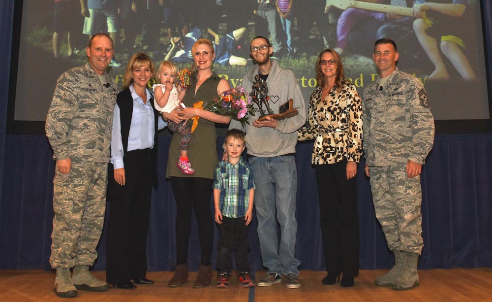 (U.S. Air Force photo by Maj. William Russell) PETERSON AIR FORCE BASE, Colo. – The inaugural 21st Space Wing Resiliency Award is presented to Staff Sgt. Ryan Meston, 4th Space Control Squadron, and his family during a commander's call at the auditorium on Peterson Air Force Base, Colo., Oct. 13, 2016. In recent years, Meston was diagnosed with two types of cancer back-to-back, but is now in remission.