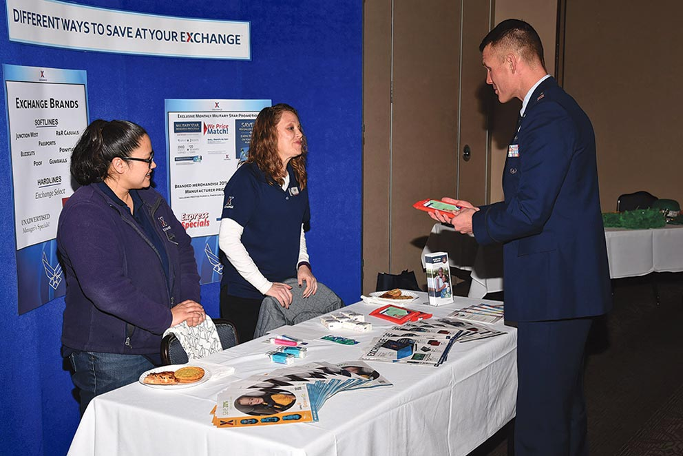 (U.S. Air Force photo by Robb Lingley) PETERSON AIR FORCE BASE, Colo. – Captain Joshua Flynn, 21st Space Wing chaplain, gathers Base Exchange information from Kristie Thomas and Kathy Dugan, Base Exchange employees, during the Financial Fair at The Club, Peterson Air Force Base, Colo., Feb. 28, 2017. The Exchange offers savings on commercial and grocery items.