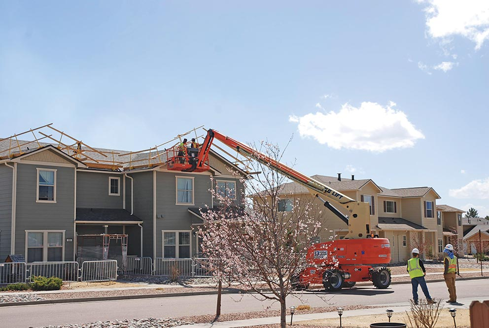 (U.S. Air Force photo by Dave Smith) PETERSON AIR FORCE BASE, Colo. — Workers use a lift to make repairs on the roof of a housing unit on Peterson Air Force Base, Colo., March 23, 2017. Thousands of windows on hundreds of housing units, along with roofing and solar panels, were damaged during the July 28, 2016, hail storm that hit the Pikes Peak Region. Crews are working extended hours to repair the damage.