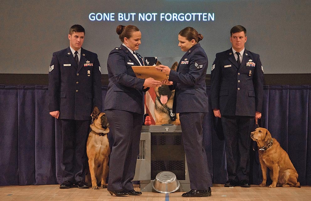 PETERSON AIR FORCE BASE, Colo. –Lt. Col. Nicole Roberts, 21st Security Forces Squadron commander, presents Senior Airman Karissa Fitzpatrick, 21st SFS Military Working Dog handler, a plaque to commemorate Fitzpatrick's MWD, Roky, career as a MWD in the base auditorium at Peterson Air Force Base, Colo., April 10, 2017. Team Pete Airmen came to memorialize Roky's legacy and military service.