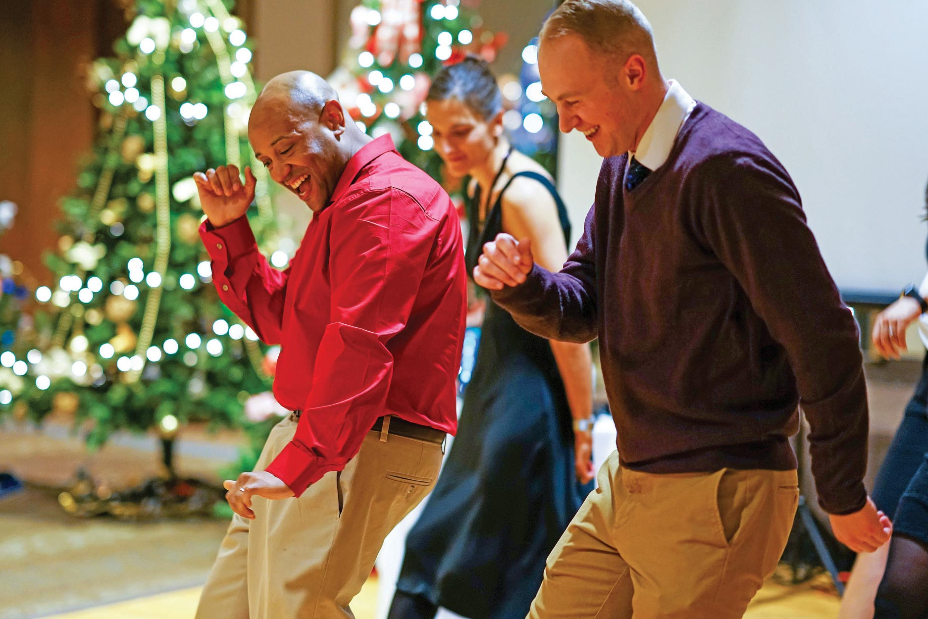 """U.S. Air Force photo by Christopher DeWitt Maj. Stephen Cash, 50th Comptroller Squadron commander, and 2nd Lt. Lucas Hash, Program Management Office program manager, dance during the Schriever Air Force Base """"Seasonal Celebrations around the World"""" holiday party at Peterson Air Force Base, Colorado, Dec. 1, 2017. Cash was one of several raffle winners to take home a prize that night."""